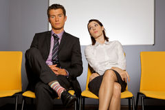 Businessman and businesswoman in waiting room Stock Images
