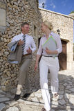 Businessman and businesswoman walking along stone building Royalty Free Stock Photos