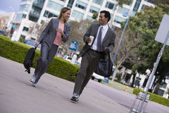 Businessman and businesswoman walking on pavement in city, carrying rucksacks, smiling (tilt) Royalty Free Stock Photography
