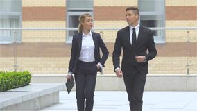 Businessman and businesswoman walking on the street of an business center, slow motion. Two business colleagues in discussion, businesspeople walking on the stock footage