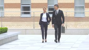 Businessman and businesswoman walking on the street of an business center. Two business colleagues in discussion, businesspeople walking on the street of an stock video