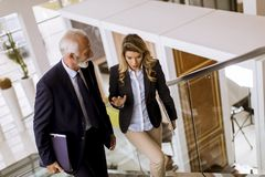 Businessman and businesswoman walking and taking stairs in an of royalty free stock photography