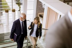 Businessman and businesswoman walking and taking stairs in an of royalty free stock photo