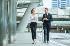 Businessman and businesswoman walking and talking on  street in city Outside Office with ,young couple discussing and eating royalty free stock photography