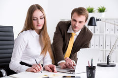 Businessman and businesswoman at work. Businessman showing something on computer, businesswoman next to him making notes, office at background. Concept of stock images