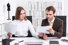 Businessman and businesswoman at work. Businessman and businesswoman sitting together and looking throuhg documents, office at background. Concept of cooperation Stock Photography