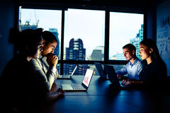 Businessman and businesswoman working with computer overtime at night Royalty Free Stock Images