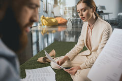 Businessman and businesswoman working with papers while sitting on floor Royalty Free Stock Photos