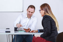 Businessman and businesswoman working with tablet. Businessman and businesswoman at the office working with tablet Royalty Free Stock Image