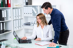 Businessman and businesswoman working together in the office Stock Image