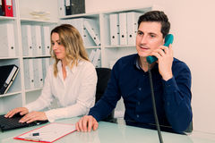 Businessman and businesswoman working together in the office Stock Photo