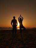 Businessman businesswoman yoga asana sea. Young businessman and businesswoman on the sea shore, standing in a yoga position, meditating at sunset Stock Photos