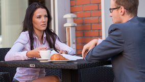 Businessman and businesswomen having a meeting in cafe. He is signing a contract. Royalty Free Stock Photo