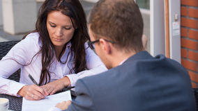 Businessman and businesswomen having a meeting in cafe. She is signing a contrtact. Royalty Free Stock Images