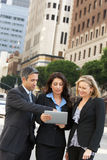 Businessman And Businesswomen Using Digital Tablet Outside Royalty Free Stock Photo