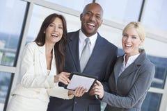 Businessman Businesswomen Using Tablet Computer. Man and two women, businessman and businesswomen interracial team using tablet computer outside in modern city Stock Photos