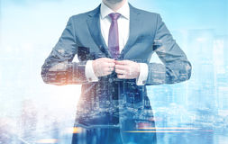 Businessman buttoning his suit in a city Royalty Free Stock Photos