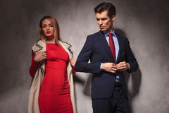 Businessman buttoning his suit and looks back at his girlfriend. Business men buttoning his suit and looks back at his blonde girlfriend wearing red dress and royalty free stock image