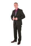 Businessman buttons up his jacket Stock Photos