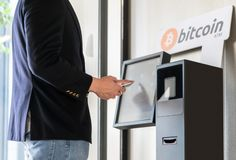 Businessman buying and transfering cryptocurrency to mobile phone from ATM machine for buying and selling cryptocurrency stock photos
