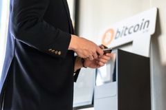 Businessman buying and transfering cryptocurrency to mobile phone from ATM machine for buying and selling cryptocurrency stock photo
