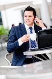 Businessman At Cafe. A young businessman sitting outside at a cafe on the phone Stock Photos