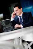 Businessman At Cafe. A young businessman sitting outside at a cafe on the phone Royalty Free Stock Images