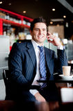 Businessman At Cafe. A young businessman sitting outside at a cafe on the phone Stock Photography