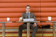 Businessman in cafe with disposable coffee cup, paperwork on table, smiling, portrait, low angle view Royalty Free Stock Photo