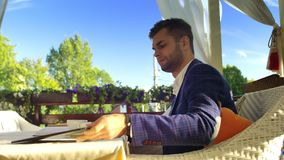 Businessman in a Cafe. A man uses a tablet, then takes a sip some coffee and leans back on the chair stock video footage