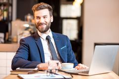 Businessman at the cafe. Portrait of a handsome businessman stricly dressed in the suit working with laptop at the modern cafe interior royalty free stock photography
