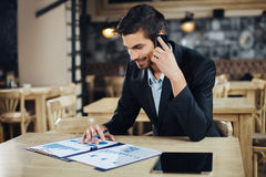 Businessman in cafe and talking on mobile phone Royalty Free Stock Photos