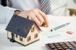 Businessman calculate the cost of building and maintaining home Stock Photography