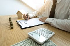 Businessman calculates sale price house business. Agent home ins stock photos
