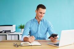 Businessman calculates tax stock image