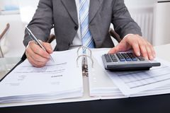 Businessman calculating bills Royalty Free Stock Photo