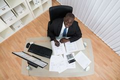 Businessman Calculating Bills In Office Royalty Free Stock Photos