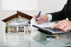 Businessman Calculating Expanses With House Model Stock Images
