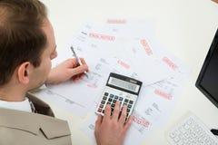 Businessman calculating financial bills stock images