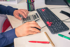 Businessman calculating the financial statements. Close up young man with calculator counting making notes at home stock photo