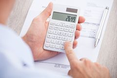 Businessman calculating invoice at desk Stock Images