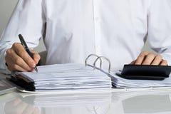 Businessman Calculating Invoice At Desk Stock Photos