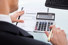 Businessman calculating invoice at office desk Royalty Free Stock Photos