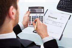Businessman calculating invoice at office desk Royalty Free Stock Photography