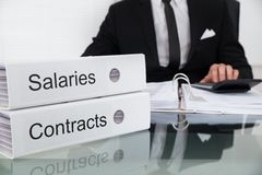 Businessman Calculating Salaries And Contracts Stock Image