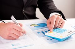 Businessman calculating sales earnings. Businessman sitting at the desk, calculating sales earnings Stock Photos