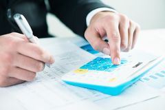 Businessman  calculating sales earnings. Businessman sitting at the desk, calculating sales earnings Stock Photography