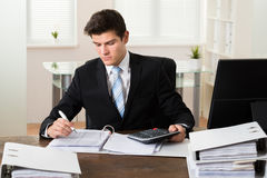 Businessman Calculating Tax In Office Stock Image