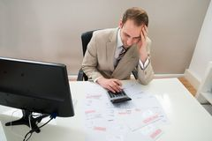 Businessman calculating unpaid bills royalty free stock images
