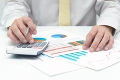 Business analysis. Businessman with calculator doing business data analysis Stock Image